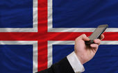 Cell phone in front national flag of iceland — Stock Photo