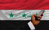 Téléphone cellulaire en front drapeau national de l'iraq — Photo