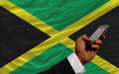 Cell phone in front national flag of jamaica — Stock Photo