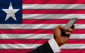 Cell phone in front national flag of liberia — Stock Photo