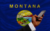 Cell phone in front flag of american state of montana — Stock Photo