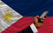 Cell phone in front national flag of philippines — Stock Photo