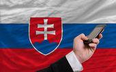 Cell phone in front national flag of slovakia — ストック写真