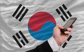 Cell phone in front national flag of south korea — Stock Photo