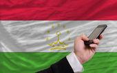 Mobilní telefon v přední národní vlajka tádžikistánu — Stock fotografie