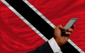 Cell phone in front national flag of trinidad tobago — Stock Photo