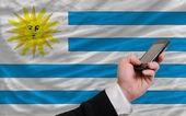 Cell phone in front national flag of uruguay — Stock Photo