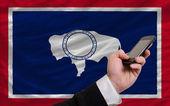 携帯電話の前にアメリカ ワイオミング州の旗します。 — ストック写真