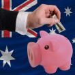 Dollar into piggy rich bank and  national flag of australia - Stock Photo