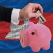 Dollar into piggy rich bank and  national flag of cambodia - Zdjęcie stockowe