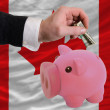Dollar into piggy rich bank and  national flag of canada - Zdjęcie stockowe