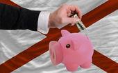 Dollar in piggy rijke bank en vlag van amerikaanse staat van alaba — Stockfoto