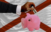 Dollar into piggy rich bank and flag of american state of alaba — Stock Photo