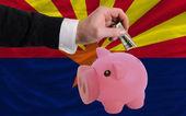 Dollar in piggy rijke bank en vlag van amerikaanse staat van arizo — Stockfoto