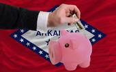 Dollar in piggy rijke bank en vlag van amerikaanse staat van arkan — Stockfoto