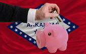 Dollar into piggy rich bank and flag of american state of arkan — Stock Photo