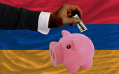 Dollar into piggy rich bank and national flag of armenia — Stock fotografie