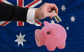 Dollar into piggy rich bank and national flag of australia — Stock Photo