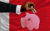 Dollar into piggy rich bank and national flag of bahrain — Stock Photo