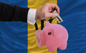 Dollar into piggy rich bank and national flag of barbados — Stock Photo