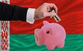 Dolar do prasátko bohaté banky a státní vlajka běloruska — Stock fotografie