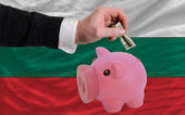 Dollar into piggy rich bank and national flag of bulgaria — Stock Photo