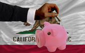 Dollar into piggy rich bank and flag of american state of calif — Stock Photo