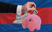 Dollar into piggy rich bank and national flag of cambodia — Stock Photo