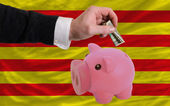 Dollar into piggy rich bank and national flag of of catalonia — Stock Photo