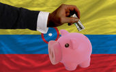 Dollar into piggy rich bank and national flag of columbia — Stock Photo