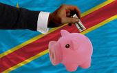 Dollar till rika piggy bank och nationella flagga i kongo — Stockfoto