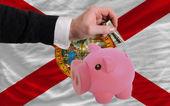Dollaro in piggy bank ricco e bandiera dello stato americano di flori — Foto Stock