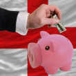 Dollar into piggy rich bank and  national flag of england - Stock Photo