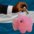 Dollar into piggy rich bank and  national flag of el salvador - Stock Photo