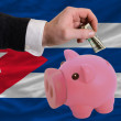 Dollar into piggy rich bank and  national flag of cuba — Photo