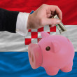 Dollar into piggy rich bank and  national flag of croatia - Stock Photo
