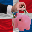Dollar into piggy rich bank and  national flag of dominican - Stock Photo
