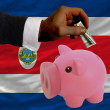 Dollar into piggy rich bank and  national flag of costarica - Stockfoto