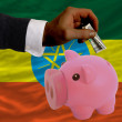 Dollar into piggy rich bank and  national flag of ethiopia - Stock Photo