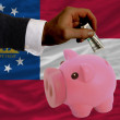 Dollar into piggy rich bank and  flag of american state of georg - Stock Photo