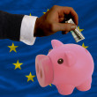 Dollar into piggy rich bank and  national flag of europe - Stock Photo