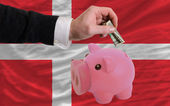 dollar into piggy rich bank and national flag of denmark — Stockfoto