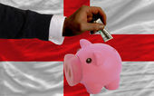 Dollar into piggy rich bank and national flag of england — Zdjęcie stockowe