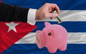 Dollar in reich sparschwein und nationalflagge kubas — Stockfoto