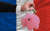 Dollar into piggy rich bank and national flag of france — Stock Photo