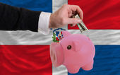 Dollar into piggy rich bank and national flag of dominican — 图库照片