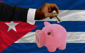 Dollar into piggy rich bank and national flag of cuba — Stock Photo