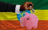 Dollar into piggy rich bank and national flag of ethiopia — Stock Photo