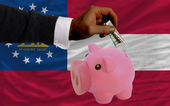 Dollar into piggy rich bank and flag of american state of georg — Stock Photo