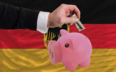 Dollar into piggy rich bank and national flag of germany — Stock Photo